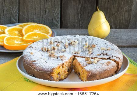 Delicious carrot cake with nuts and raisins on a white plate.