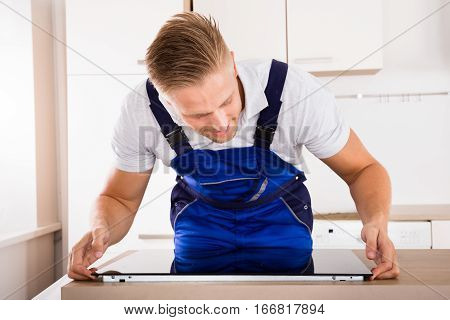 Smiling Male Repairman Installing Induction Cooker In Kitchen