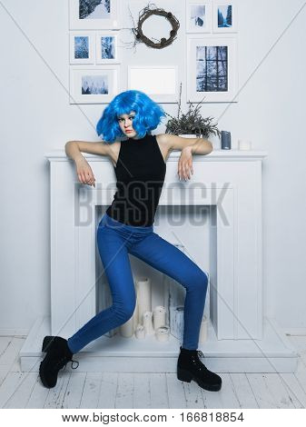 Girl in color wig Young tall girl in a color wig posing on white background fireplace in the interior