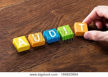 Close-up Of An Audit Concept On Colorful Blocks At Wooden Desk. Business Taxes And Accounting Concept