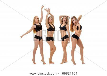 Graceful pretty fitness trainers in black tops and pants posing in studio