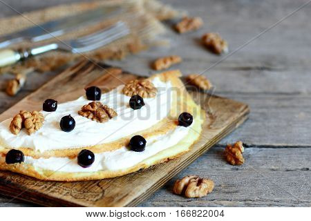 Fried stuffed omelet. Homemade omelet with soft cheese, walnuts and blackcurrant on a wooden board. Simple and tasty dish using egg. Closeup