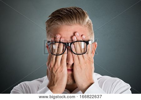 Man's Hand Over The Face With Eyeglasses Over Grey Background