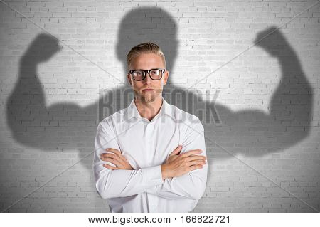 Conceptual Young Businessman Standing In Front Of Gray Background With Muscular Shadow