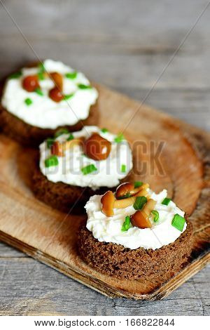 Small open sandwiches on a wooden board. Sandwiches with rye bread, soft cheese, canned mushrooms and green onions. Wooden background. Vertical photo. Closeup