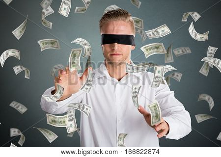 Young Blindfolded Businessman With Falling Money Against Grey Background