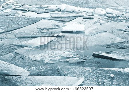 Fragments of ice on the surface of the frozen river.