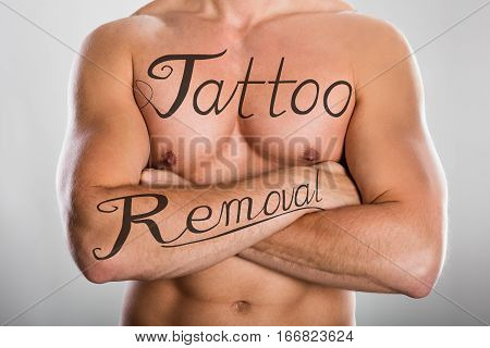 Tattoo Removal Text On Shirtless Man's Chest And On His Arm Against Grey Background