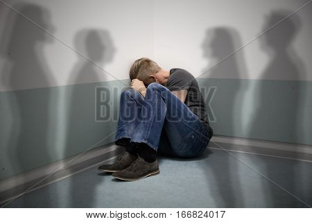 Scared Man Sitting In The Corner Of A Room With People Shadows On Wall