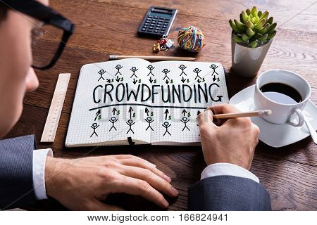 High Angle View Of Businessperson Drawing Crowdfunding Concept On Notebook At Wooden Desk