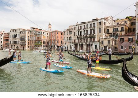 Venice, Italy - July 24, 2016: Group of sporty active tourists stand up paddling on sup boards in guided organized group on historical Grand Canal on 24th of July in Venice, Italy.