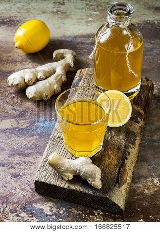 Homemade fermented raw ginger lemon kombucha tea. Healthy natural probiotic flavored drink.