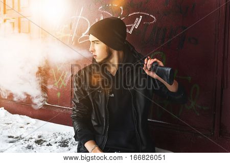 Portrait of the man in black jacket and with gun. He is smoking.
