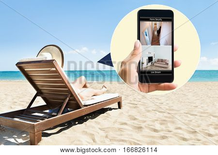 Woman Relaxing On Lounge Chair At Beach Looking At Security System On Mobile Phone