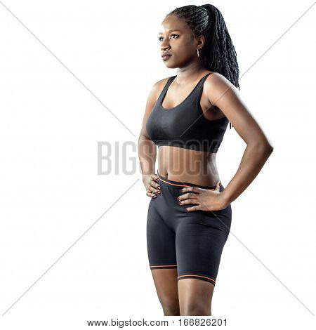 Medium shot of attractive african teen girl in sportswear standing with hands on hips. Young woman looking aside isolated on white background.