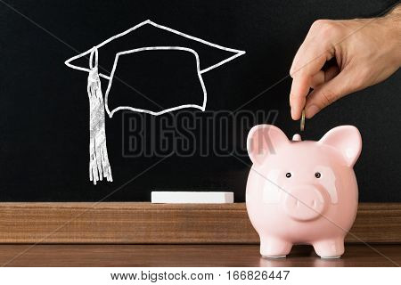 Person Hand Inserting Coin In Piggybank With Graduation Cap Drawn On Blackboard At Background