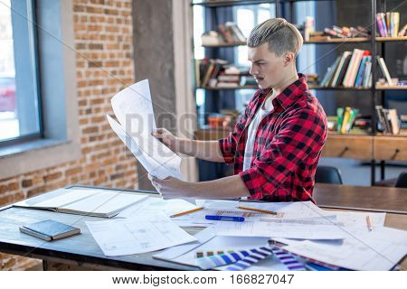 Pensive yound male architect examining blueprints in office