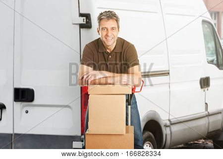Smiling Delivery Man Or Mover Leaning On Cardboxes In Front Of The Van