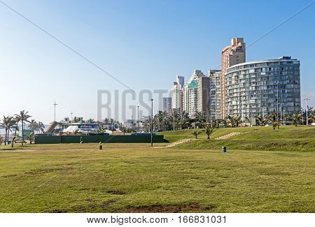 Empty Grass Verge Against City Skyline And Blue Sky