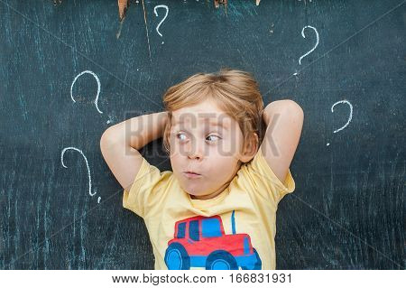 Top View Of A Little Blond Kid Boy With Question Mark On Blackboard. Concept For Confusion, Brainsto