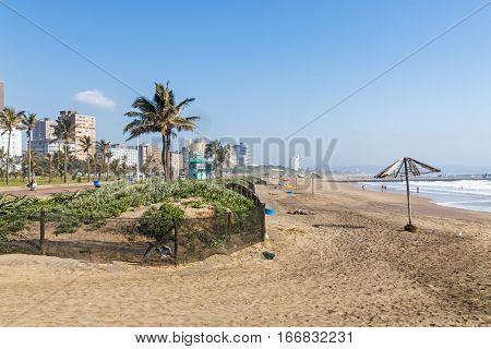 Dune Vegetation And Empty Beach Against City Skyline