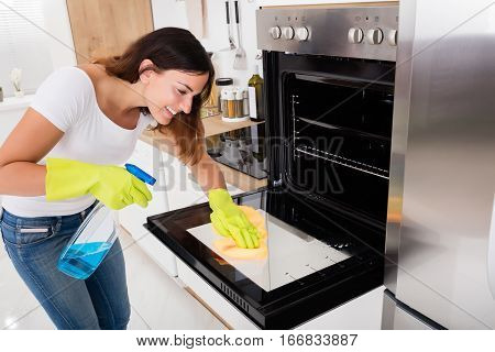 Young Happy Woman Cleaning The Glass Door Of Oven In Kitchen