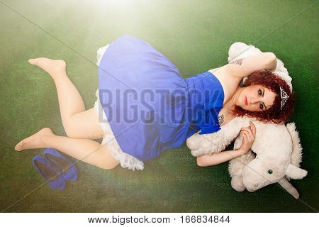 Princess and unicorn. Young girl in a fairy tale. A young girl dressed in blue dress and crown on her head is lying on a green lawn, over a puppet unicorn. Light point at the top.