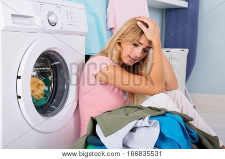 Unhappy Stressed Woman Showing Signs Of Fatigue Looking At Pile Of Clothes Near Washing Machine