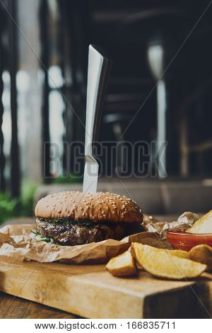 Fast food dish on served table in restaurant. Appetizing meat burger in craft wrapping paper with knife in it, potato wedges with tomato sauce. Takeaway meals, vertical composition.