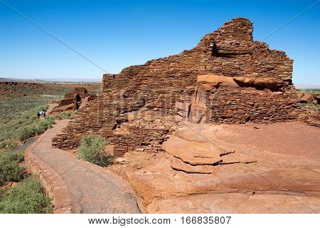 FLAGSTAFF ARIZONA - JUNE 14 2016: Tourists walk through ruins built by Native American Pueblo Indians at Wupatki National Monument near Flagstaff Arizona USA on June 14 2016.