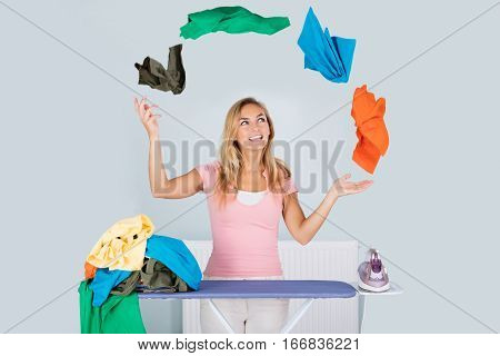 Young Smiling Woman Juggling With Colorful Clothes Near Ironing Board At Home