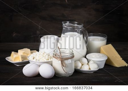 Selection of Dairy products on wooden table. Cottage cheese yogurt Sour cream milk egg cheese and butter. Country style.