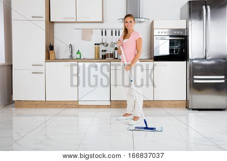 Portrait Of Young Smiling Cleaning Service Woman With Mop Standing In The Kitchen At Home