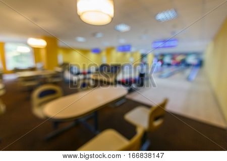 Bowling blurred background. Unfocused interior of bowling alley with seating area. Leisure activity club bokeh