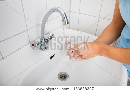 Woman Applying Soap While Washing Hands In Basin With Open Tap