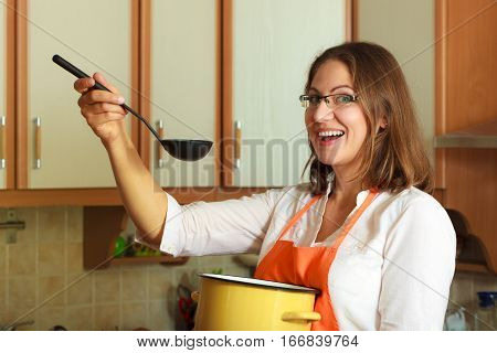 Housewife tasting soup meal dinner. Middle aged woman holding spoon ladle and pot. Housekeeper wearing orange apron preparing food.