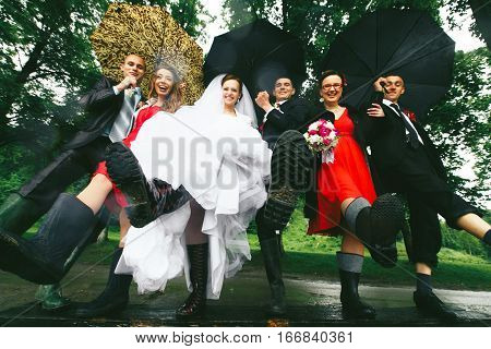 Newlyweds And Their Friends Hold Legs In The Gumboots Up