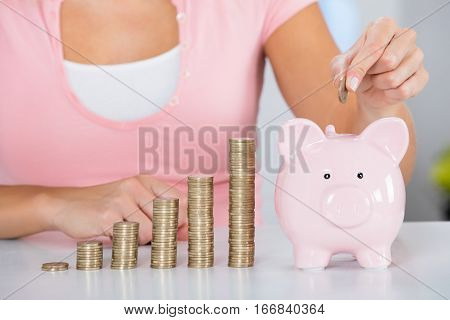 Close-up Of Young Woman Inserting Coin In The Piggybank Near Stack Of Coins On Desk