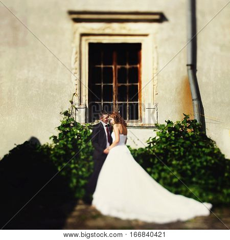 Fiance Holds Bride's Hands Standing In The Front Of An Old Building