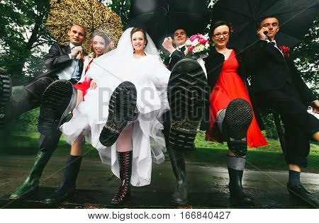 The Soles Of Gumboots On The Legs Of Newlyweds And Their Friends