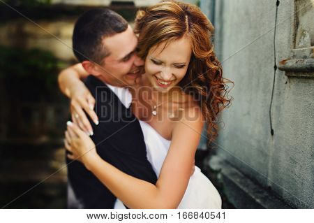 Fiance hugs tightly a smiling bride on the street