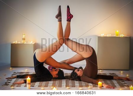 Two Young Women Doing Yoga Asana Supported Shoulderstand On Plaid In Cozy Room With Candles