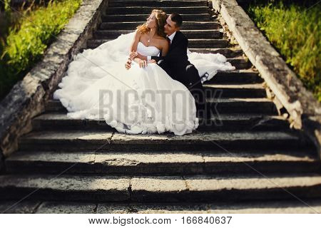 Bride Sits On The Fiance's Knees On The Old Stone Footsteps