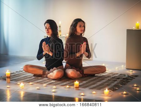 Two Young Women  Meditating In Lotus Pose With Hands In Namaste On Plaid In Cozy Room With Candles