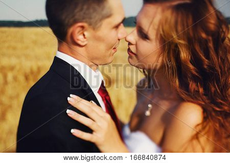 Bride Reaches To Kiss A Fiance While Wind Blows Her Hair