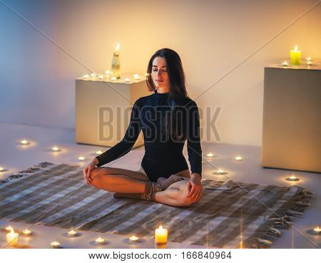 Young Beautiful Woman Meditating On Lotus Pose In Cozy Room With Candles