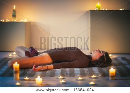Young Beautiful Woman Doing Yoga Asana Sleeping Supine Lotus Pose On Plaid In Cozy Room With Candles