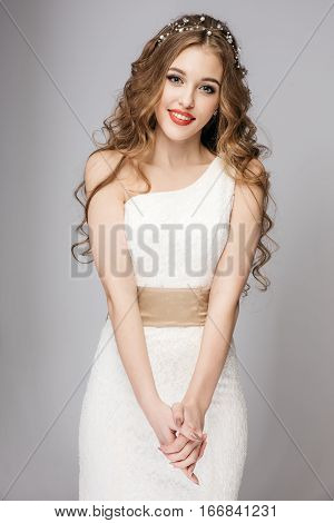 Slim beautiful woman with long hair wearing wedding dress isolated on gray