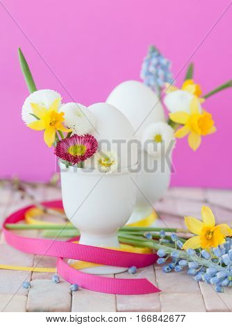 White eggs in cups with colorful spring flowers