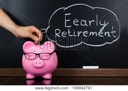 Person Hand Inserting Coin In Piggybank Showing Retirement Concept On Blackboard